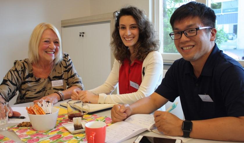 Ina Kars (links), Tugce Yakit, en Barry Kuo vermaken zich in het Taalcafé. (Foto: Rob Weekers).
