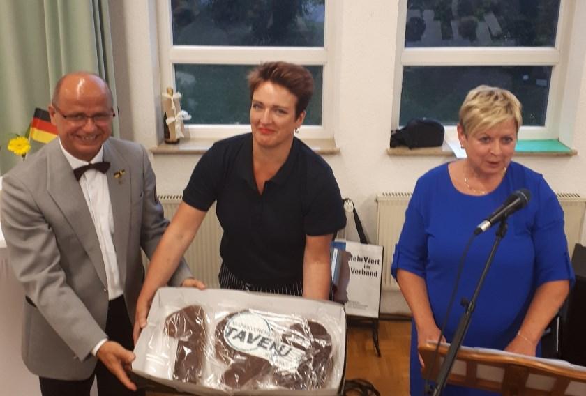 Margot Kuzee en Ria Sterrenburg overhandigen de bijzondere Schoonhovense Fonteynkoek aan voorzitter Klaus Walter van Musikverein Stadtkapelle Weil der Stadt.