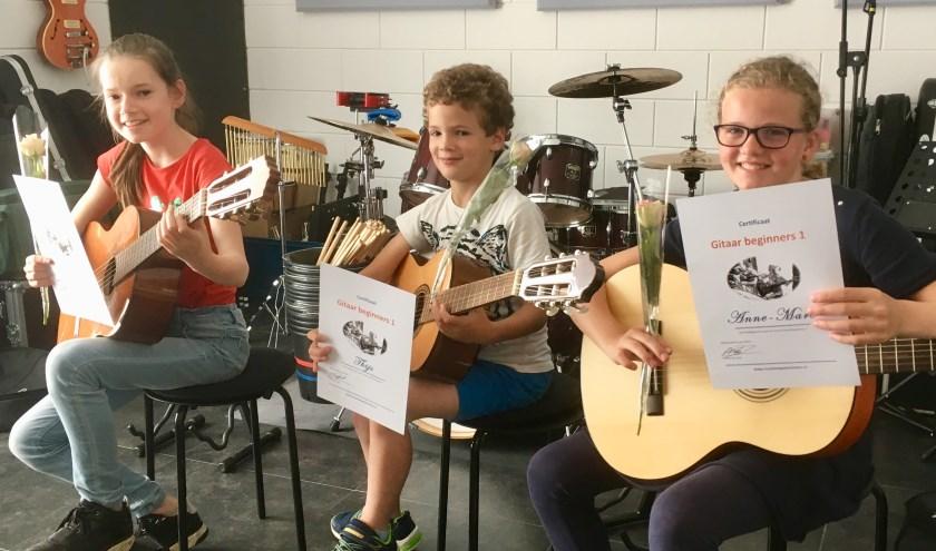 De cursisten van Gitaar Beginners 1 met hun certificaat: Diana, Thijs en Anne-Mare