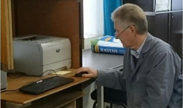 Op de foto Jan met zijn vaste grijze stofjas aan op zijn vaste plaats achter het beeldscherm