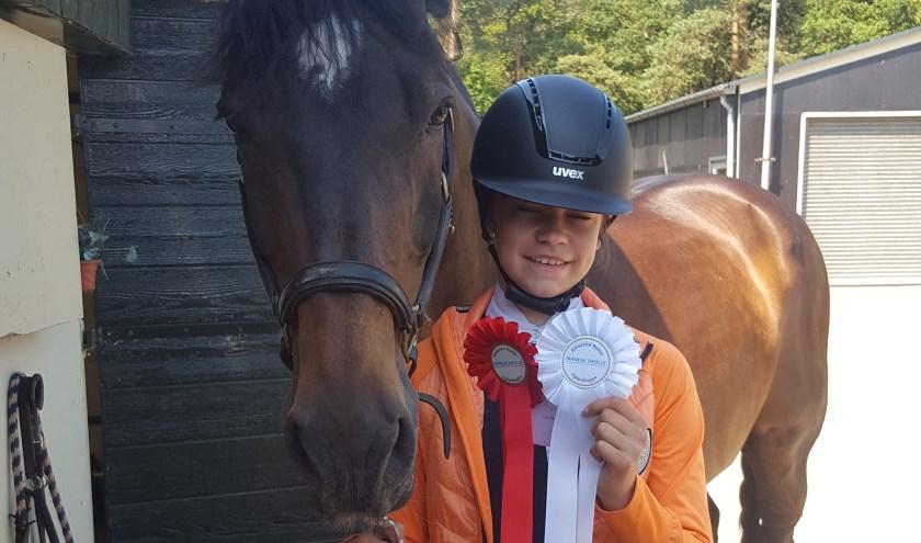 Amke toont trots haar gewonnen rozetten.