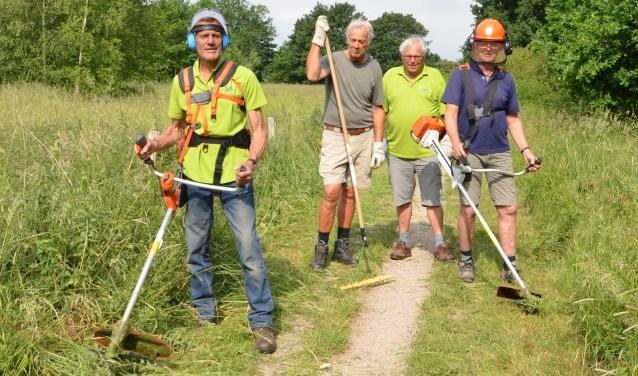 De houthakkers: Henk van Werkhoven. Wim van Setten, Peter Heijnis en Frans Hoving maaiden het gras om de wandelpaden goed begaanbaar te houden. Co Maas was deze week op vakantie. FOTO: Ben Blom