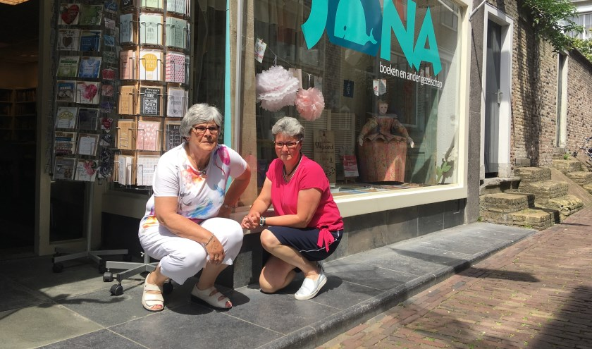 Riet Hanse (links) en Henriëtte de Bakker voor hun winkel in de Visstraat in Zierikzee. Wie komt deze dames en de andere vrijwilligers helpen? FOTO: Gerrit van Loon