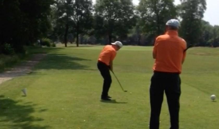 Een vrijwilliger begeleidt een golfer met een beperking.