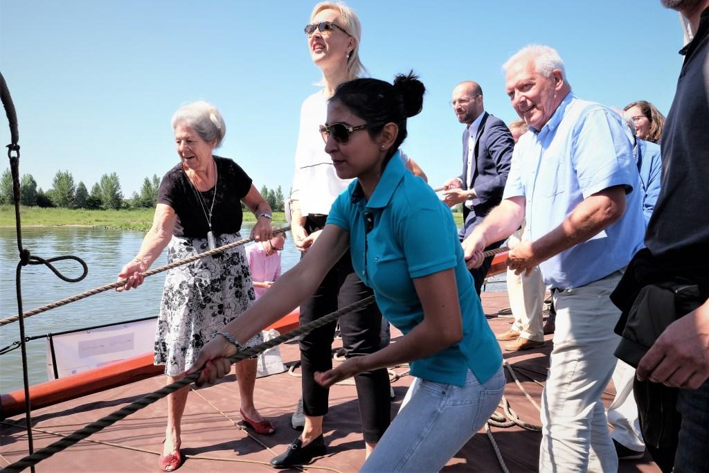 Mevrouw Jordaan links uit Rhenen helpt mee om de zeilen te hijsen.  © Persgroep