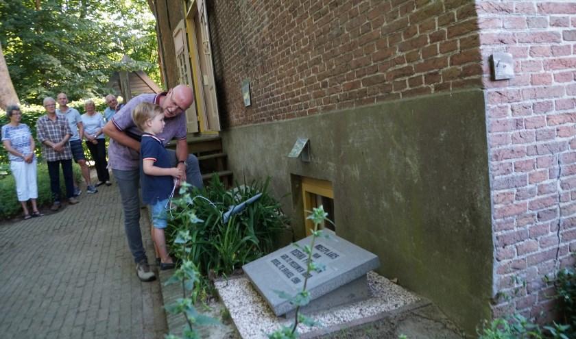 Willem (5) leest samen met Ap de With van de historische vereniging de gedenkplaat bij de grafstenen van zijn betovergrootouders.