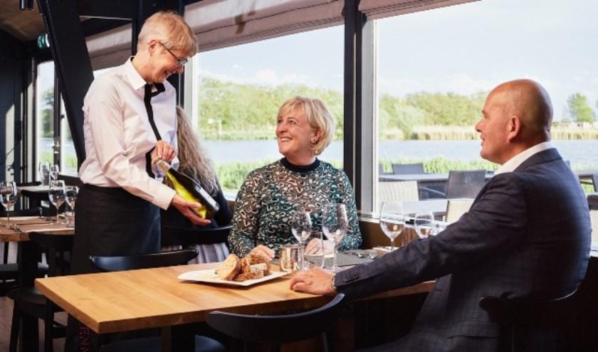 Serveerster aan tafel met wijn.