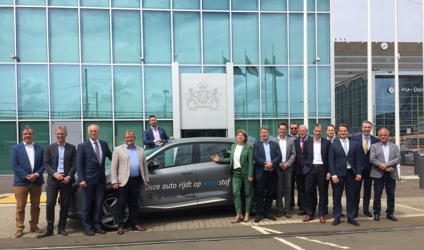 Na afloop van de bijeenkomst op het Ministerie werd een groepsfoto gemaakt bij een op waterstof rijdende auto op de foto. (foto: pr)