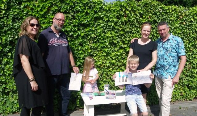 Bart Hoonhout (7) met zijn tekeningen van verdrietige vogels in het Spoorbos. Rechts ouders Carlo en Mariëlle Hoonhout, links Claudia en Miguel Rombaut met Amy (4).