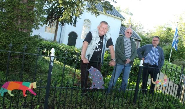 Peter Hollestelle, Rudy van Buynder en Frans Borggreve met de Katse Katten aan het hek bij de Katse kerk. FOTO: LEON JANSSENS