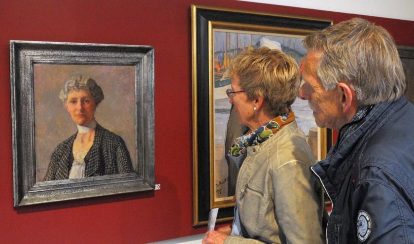 Bezoekers bij het portret dat Jo Koster maakte van Antoinette de Savornin Lohman-Gleichman. (foto: Voerman Museum Hattem)