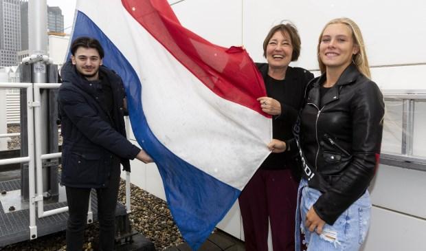 Wethouder Saskia Bruines hijst de vlag met de geslaagde eindexamenkandidaten Ibrahim en Danique.
