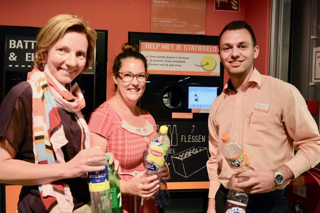 Filiaalmanager Erik Rustenhoven (r) met de dames Ilse van Dalen en Francis van Tilburg bij de Coop de plaats waar zij hopen dat er veel lege flessen worden ingeleverd voor hun speeltuin.  © Persgroep