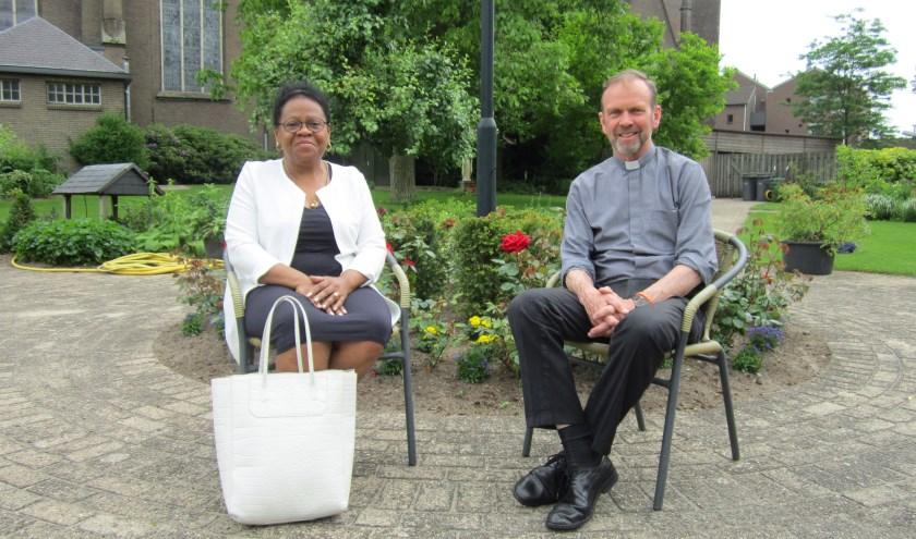Rina Doran en pastoor Roland Kerssemakers in de prachtige parochietuin waar aanstaande zondag na de mis tien katholieke nationaliteiten elkaar bij een multiculturele maaltijd zullen ontmoeten.