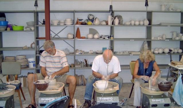 Cursisten oefenen het draaien van potten.