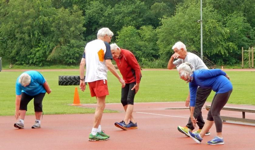 Huub Vaessen (2e van links) helpt bij de  warming-up op woensdagochtend bij Atletiekvereniging Fit. FOTO:: Asta Diepen Stöpler