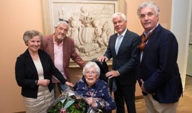 Wethouder Rinette Reynvaan en directeur Peter Schoon en de familie bij een Bovendeurstuk met allegorie op de stad Dordrecht. (foto: pr)
