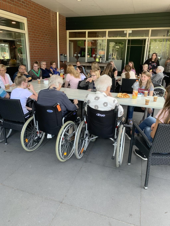 Leerlingen en ouderen dagvoorziening met elkaar in gesprek onder het genot van een kopje koffie Foto: mayke wijlens © Persgroep