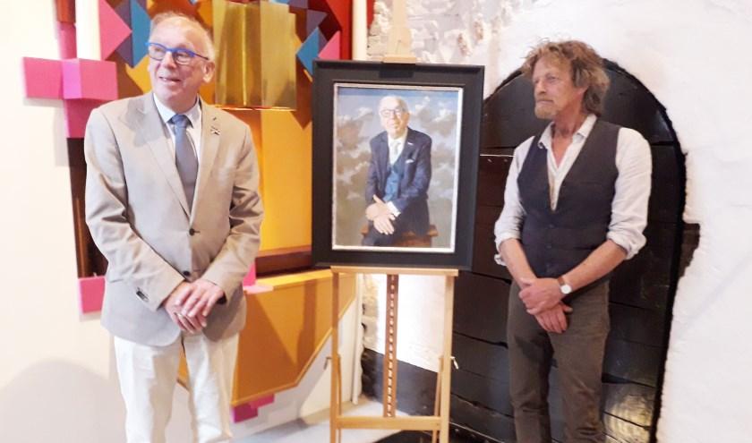 Maarten Seijbel poseert met kunstenaar Kenne Grégoire (r.) naast zijn portret. (Foto Margaretha Coornstra)
