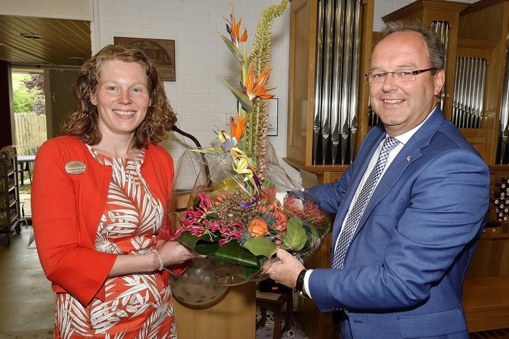 Dhr. Stoop overhandigd Marianne de Vries een mooi bloemstuk. Foto: Jan van Arend © Persgroep