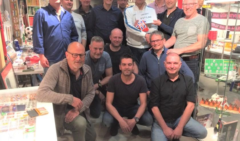 UB Oldies biedt museumeigenaar Fred Baars (wit shirt) 175 euro aan voor de kankerbestrijding