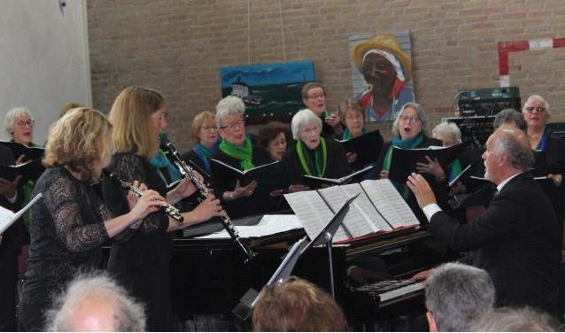 Het BaerneKoor tijdens het Lenteconcert met rechts dirigent Hans Cok en links Hanneke Meijer (dwarsfluit) en Monique Kruijdenberg (klarinet). Foto CultuurLocaal.