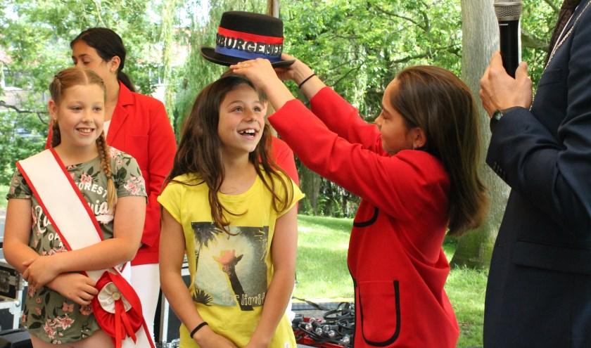 Julia Bobeldijk krijgt de burgemeesters hoed opgezet door Zoë Gude, haar voorgangster. Links wethouder Femke van der Veer. FOTO: LEON JANSSENS
