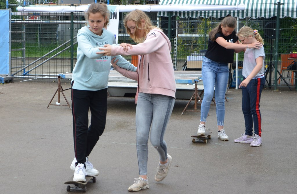 Door twee experts werd de kinderen geleerd om stapje voor stapje het skateboard eigen te maken. De methode die gebruikt werd is ook geschikt om onderling elkaar te helpen trainen.  © Persgroep