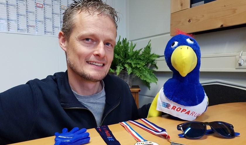 Jeroen Bouman laat enkele medailles zien. Zijn familiebedrijf levert sinds kort ook alle merchandising-artikelen, zoals de pluche Roparun-vogel.