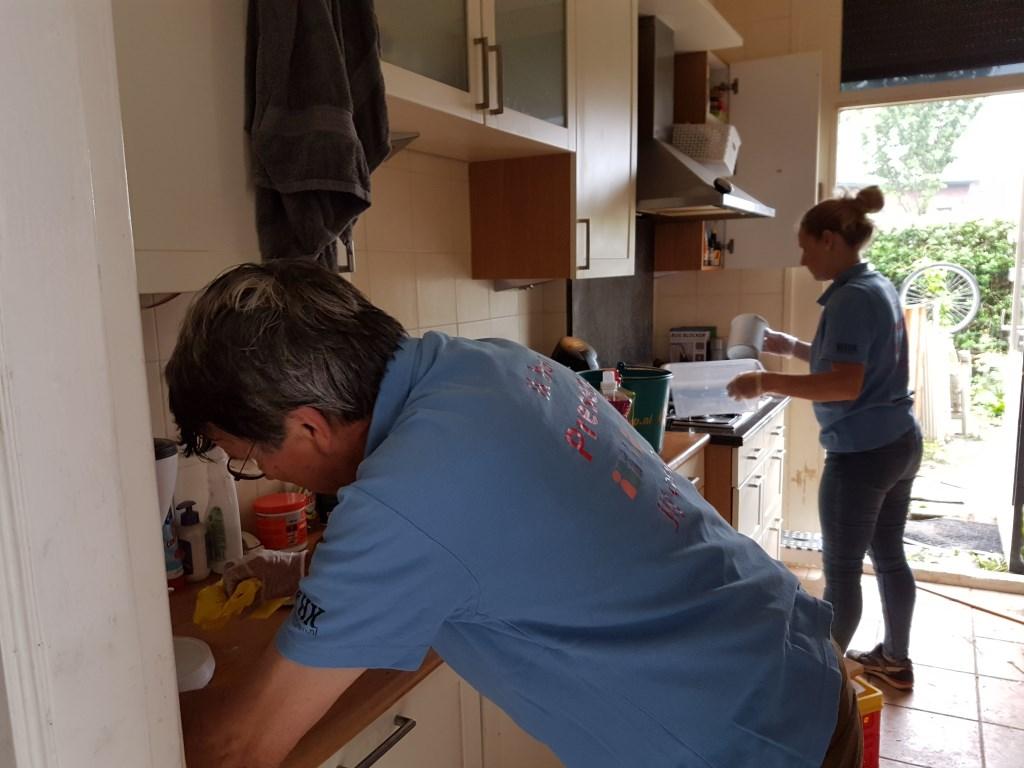 Twee vrijwilligers ruimen de keuken op en maken alles schoon Foto: Present Winterswijk © Persgroep