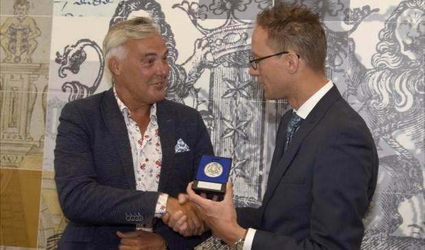 Jan de Wild (L) krijgt de erepenning van Gouda uitgereikt door wethouder  Thierry van Vugt. Foto: Marianka Peters