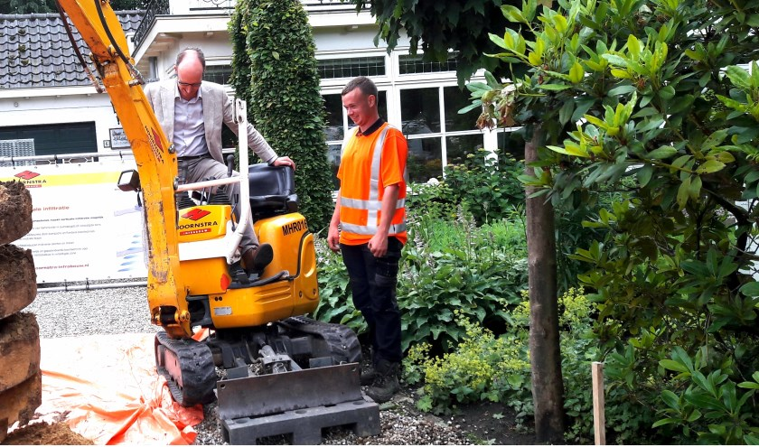 Wethouder Lex Hoefsloot zit wat onwennig op zo'n grote gele machine. (foto: Wout Schotsman)