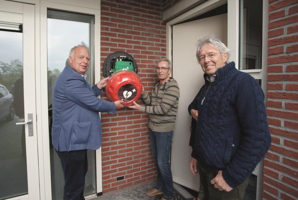De AED wordt opgehangen door vlnr: Jan Terberg (voorzitter Wijkraad Beekenoord), Erwin Schollen (wijkbewoner) en Ed Janssen (voorzitter Stichting 6 minutenzone Westervoort).