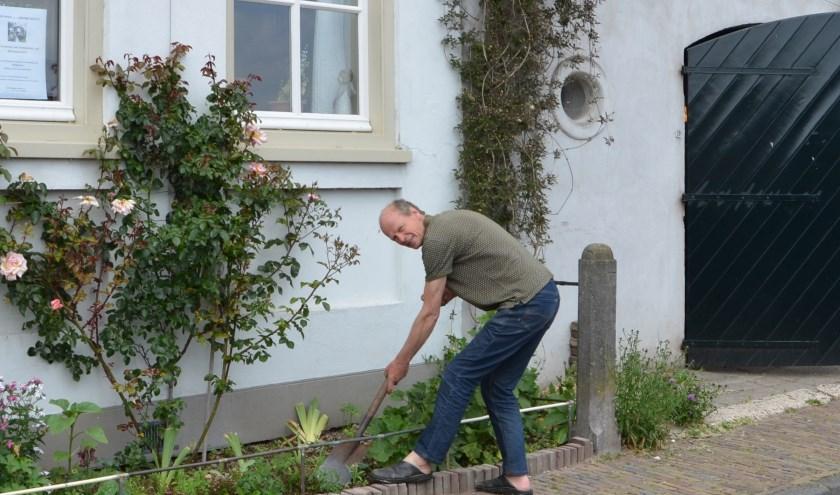 Initiatiefnemer Lodewijk Bergsma  had juist tegels gelicht en vervangen door groen, toen we belden. Hier maakt hij het klusje af. FOTO: Ben Blom