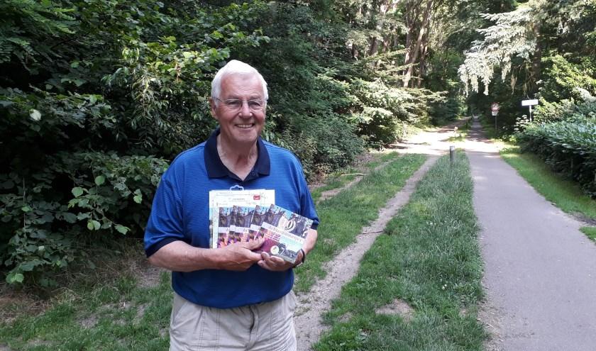 Henny Dokter met een aantal Achterommetjes in zijn hand; het toeristische informatieboekje dat 10 jaar bestaat. (foto: Ceciel Bremer)