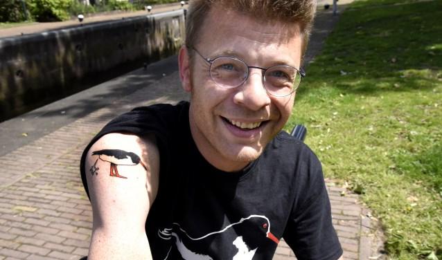 D66-burgerraadslid Bram Talman is blij met zijn tatoeage van schijtekster Cor. Foto: Marianka Peters