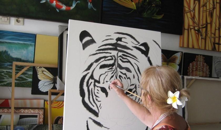 Diny bezig met een schilderij op Bali