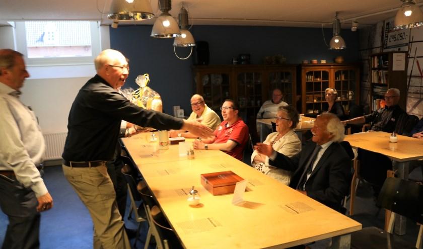 Van links naar rechts Jan van de Maat, net niet zichtbaar Gerhard Baan en Johan Nijzink. Achter de tafel zitten Lien Kootstra en Jan Velnaar die de zuivelmand krijgen aangeboden. Foto: Jan Joost.