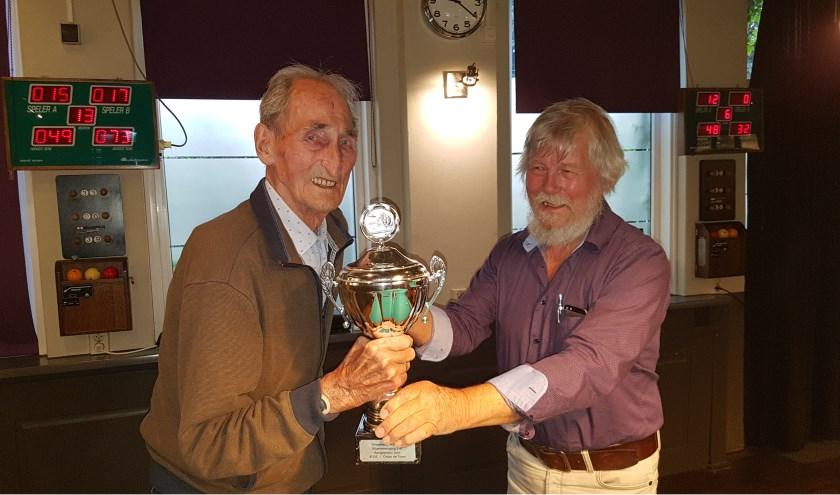 Jan straatman (89 jarige) ontvangt de beker uit handen bestuurslid Joop Schotten.