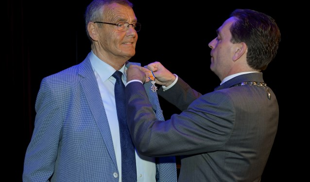 Het lintje wordt door burgemeester Michel Bezuijen bij Peter opgespeld.