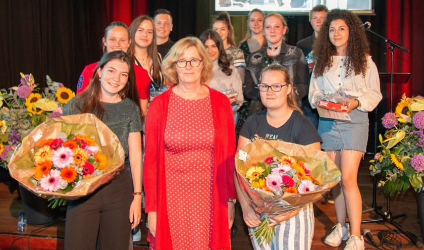 Op de voorgrond de awardwinnende leerlingen Julie Overduin en Marlot Bolk met in hun midden Ypkje Grimm van de gemeente Enschede. Op de achtergrond de andere genomineerde leerlingen.