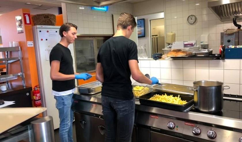 Tom Hoezen en Kamiel van Langeraad bakken ze bruin in de keuken van de Rabobank. FOTO: Cleopatra Pavlovic