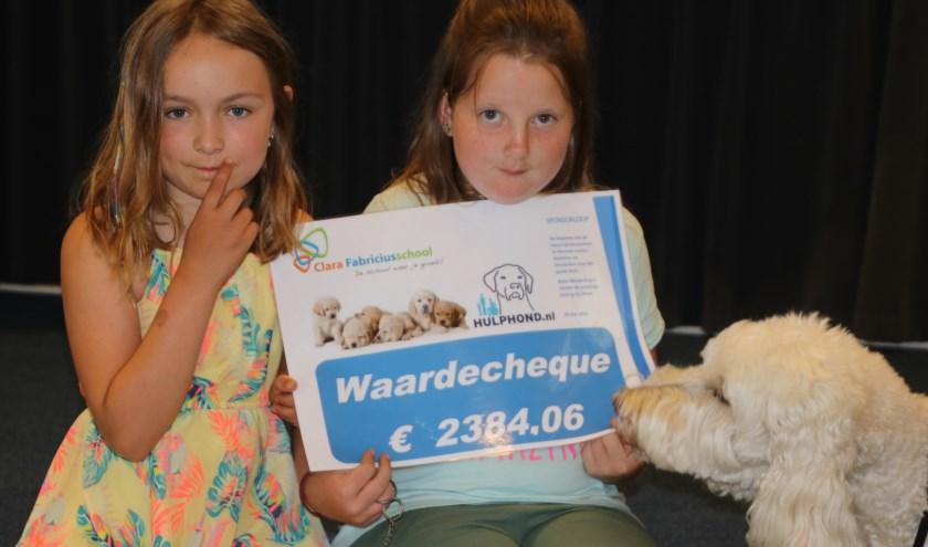 Marieke en Wendy overhandigen de waardecheque aan Nora, hulphond van Mirjam, ambassadeur van Stichting Hulphond