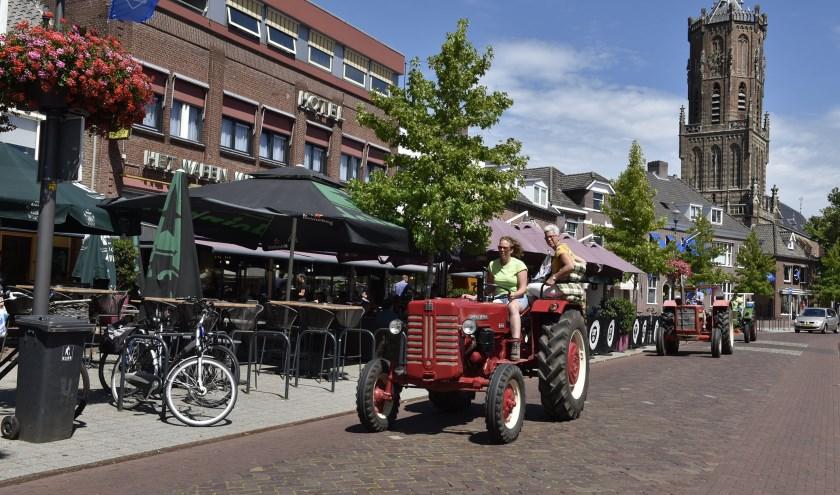 Hilde Müskens uit Groesbeek tuft met de tractor door het centrum van Elst. Ze geniet van de jaarlijkse tractorvierdaagse. (foto: Ellen Koelewijn)