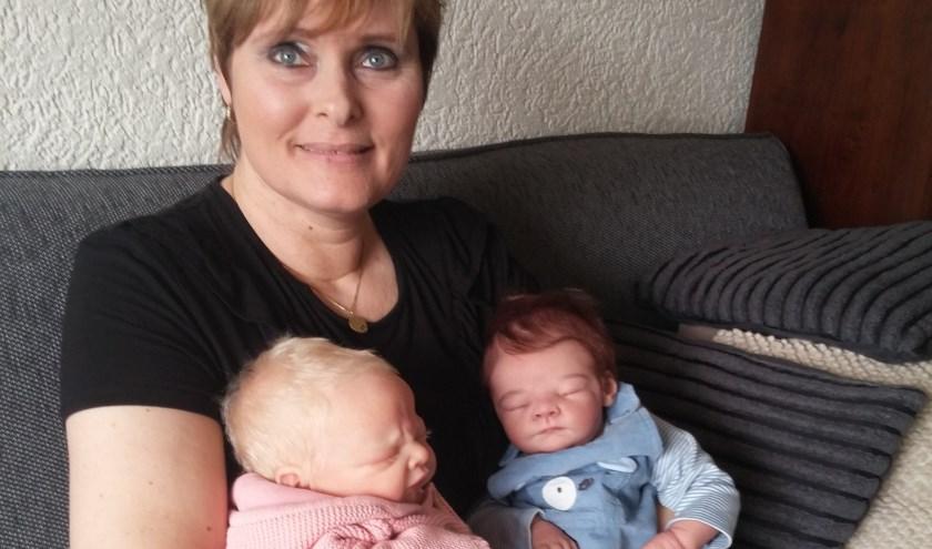 Anouska Kusters speelt niet met de poppen, maar brengt ze tot leven. Voor de foto wil ze wel met de reborns op schoot poseren. In het roze een vinylpop, in het blauw een siliconenpop. 'Het is gewoon mijn hobby.'