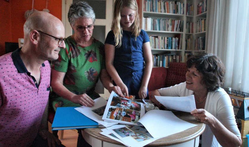 Joost, Saskia en Rozemarije Schippers bekijken samen met Carolien de Kruif de foto's van voorgaande jaren. Ze verheugen zich enorm op de komst van Bernadett Lasaar en Emöke Veres.