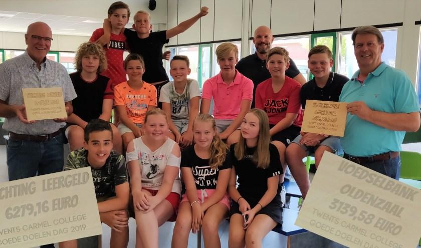 Klas 1B5 en hun docent Ben Jansen van de Potskampstraat overhandigden de cheques aan Martin Spit van stichting Leergeld en aan Jan Smudde van Voedselbank Oost-Twente.