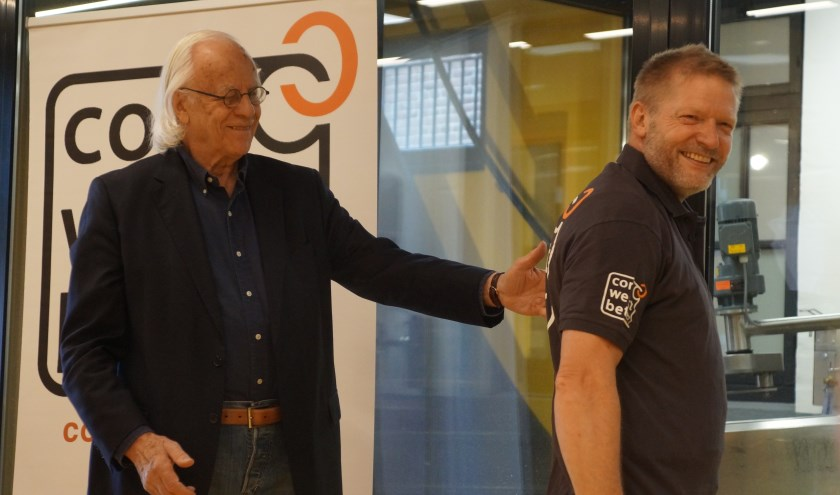 Onder goedkeurende blik van Bram van der Vlugt showt de immer lachende Cor Remmerswaal het nieuwe t-shirt van Cor Werkt Beter!