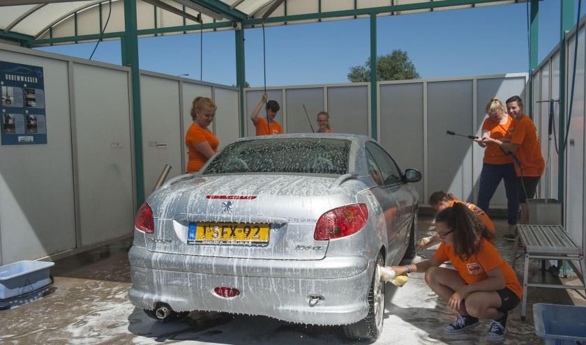 De leerlingen van Het Westeraam maken er echt werk van een auto te poetsen. De opbrengst is voor KiKa. (foto: Ellen Koelewijn)
