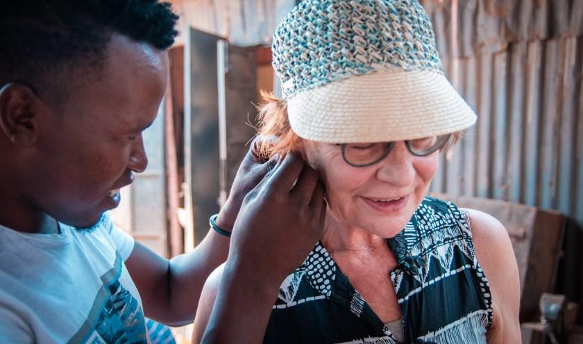 Maker van fairtrade sieraden helpt reiziger met het indoen van oorbel